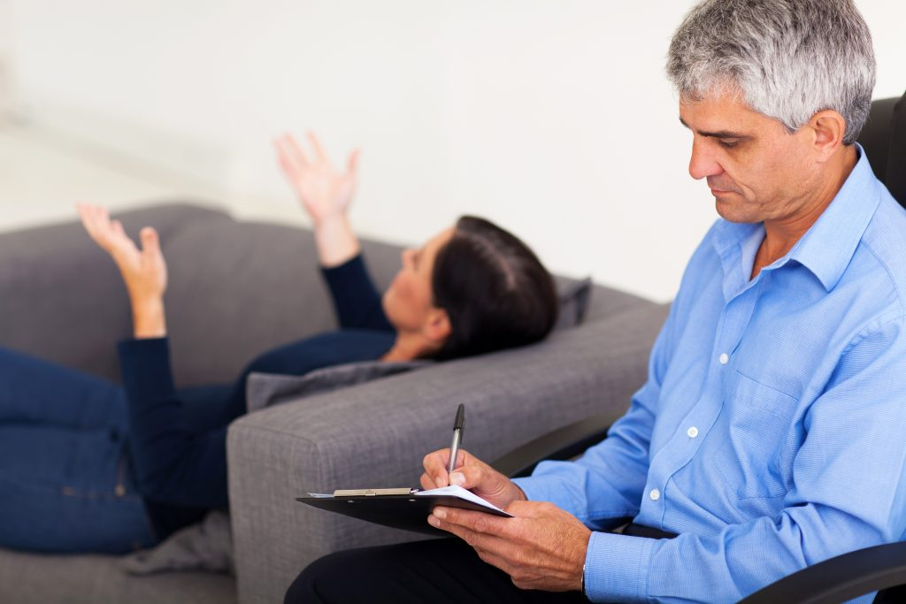 middle aged male therapist consulting female patient in office